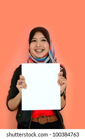 Portrait of a beautiful Muslim woman holding a white paper with smile, isolated on orange background