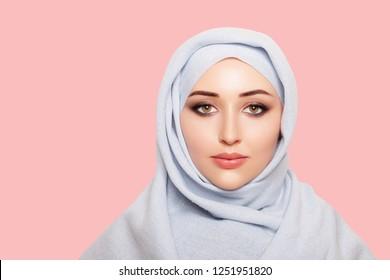 portrait of beautiful musliman asian woman. pink lips. beautiful muslim girl is wearing hijab. Islamic fashion. isolated. Muslim Girl in Hijab with Perfect Makeup. pink background - Image