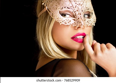 Portrait of a beautiful mysterious blond woman wearing golden mask.