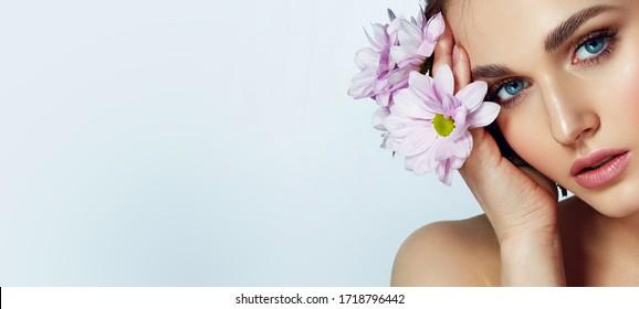 Retrato de una hermosa chica natural de ojos azules con flores de lila en el medio silvestre. maquillaje desnudo.