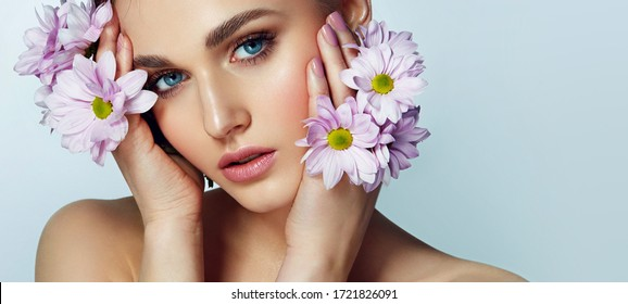Portrait of a beautiful natural blue-eyed girl with lilac flowers in the wild. Nude make-up.