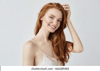 Portrait of beautiful natural redhead girl smiling looking at camera.