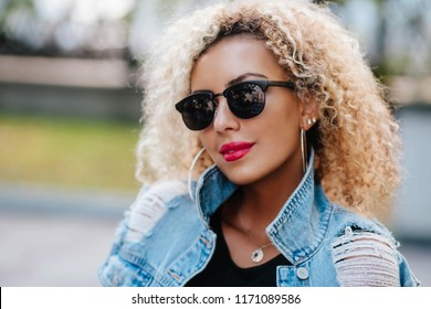 Portrait of a beautiful natural young African woman with afro in sunglasses smiling happiness