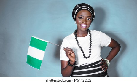 Portrait of beautiful Nigerian woman dressed in Tiv traditional attire with a flag of Nigeria