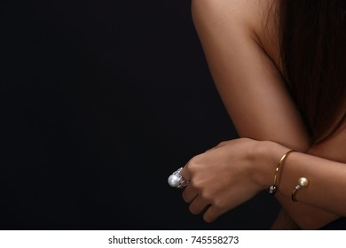 Portrait of beautiful nude long straight black hair woman with pearl necklace accessories. Naked sexy girl with smooth skin on her body over dark background, not show face