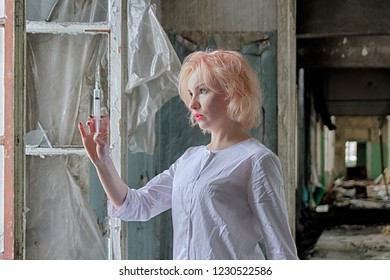 Portrait of beautiful nurse or doctor with blond hair, bright makeup  and syringe in hand standing near the window in abandoned medical clinic or asylum, get ready to make an injection