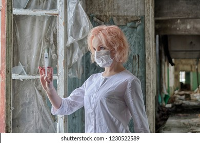 Portrait of beautiful nurse or doctor in mask with syringe in hand standing near the window in abandoned medical clinic or asylum