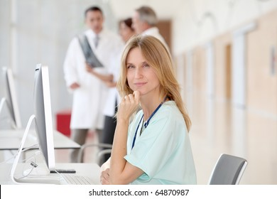 Portrait of beautiful nurse in front of medical people