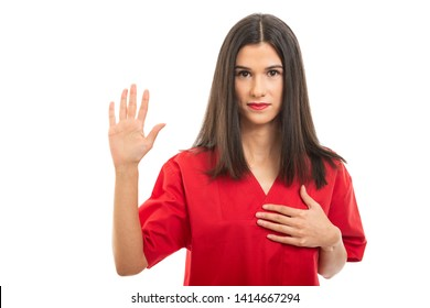 Portrait of beautiful nurse wearing red scrubs taking oath gesture isolated on white background with copy space advertising area