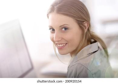 Portrait of beautiful office-worker sitting at desk