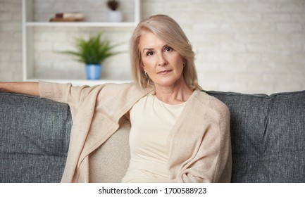 Portrait of beautiful older blonde woman is sitting on a sofa at home