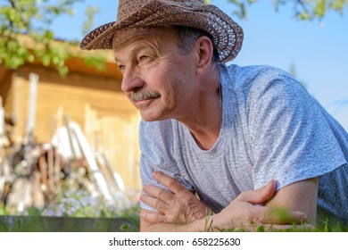 Portrait of beautiful older man Lies on the grass smiling and looking at the camera.
