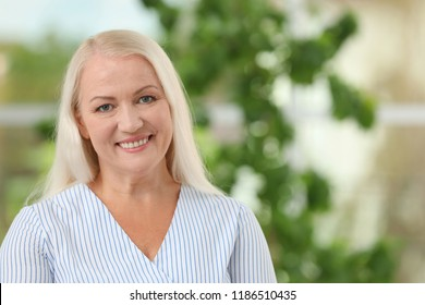 Portrait of beautiful older woman against blurred background with space for text