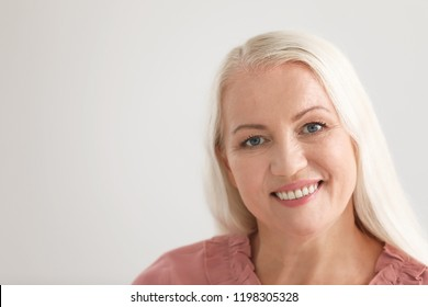 Portrait of beautiful older woman against light background with space for text