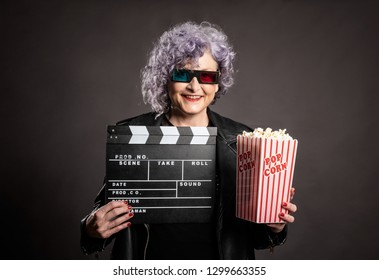 portrait of beautiful older woman holding popcorn and movie clapper on a gray background