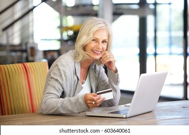 Portrait of beautiful older woman with laptop computer and credit card