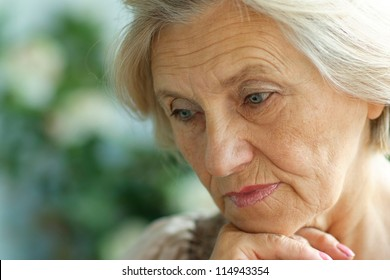 portrait of a beautiful older woman on a summer background