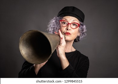 portrait of beautiful older woman shouting with an old megaphone on a gray background