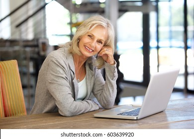 Portrait of beautiful older woman working laptop computer indoors
