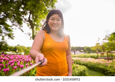 Portrait of beautiful overweight Asian woman relaxing at the park in the city of Bangkok, Thailand