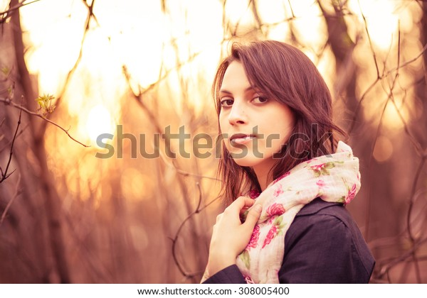 Portrait of a beautiful pensive girl in a park at sunset, warm colors, closeup