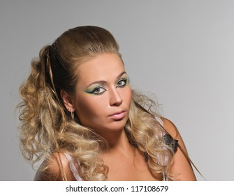 portrait of beautiful peroxide blonde girl with coiffure on grey background