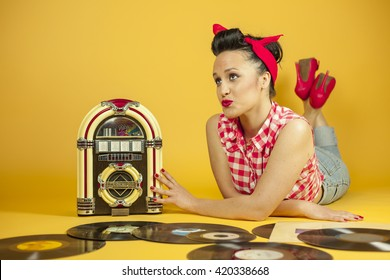 Portrait beautiful pin up listening to music an old jukebox radio, with vynil LP records, isolated yellow background