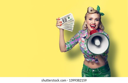Portrait of beautiful pinup girl. Happy excited smiling woman holding cash money banknotes and megaphone, pinup style. Blond model - retro fashion and vintage. Yellow color background. Copy space.