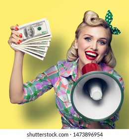 Portrait of beautiful pinup girl. Happy excited smiling woman holding cash money banknotes and megaphone, pinup style. Blond model - retro fashion and vintage. Yellow color background.