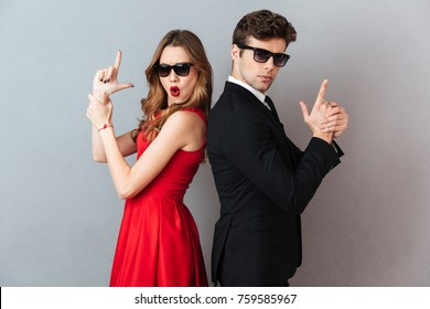 Portrait of a beautiful playful couple dressed in formal wear and sunglasses standing back to back and showing gun gesture over gray wall background