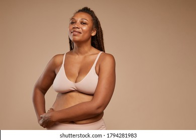 Portrait of beautiful plump woman in underwear smiling at camera isolated on brown background
