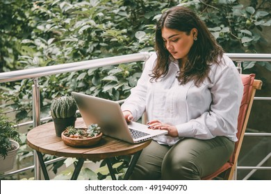 Portrait of beautiful plus size girl working on her laptop on balcony or terrace of cafe. Toned picture