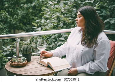 Portrait of beautiful plus size girl reading a book on balcony or terrace of cafe. Toned picture