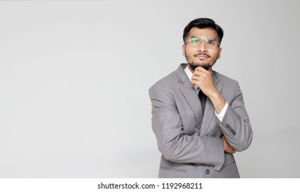 Portrait of the beautiful posing in gray jacket standing with crossed hands against gray backdrop in a studio with crossed arms on chest, planning, thinking new projects. copy space & banner.