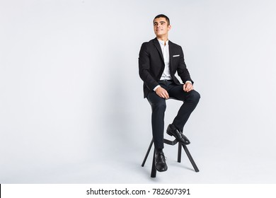 Portrait of the beautiful posing in a Studio. White background, isolated. Stylish business man, Stylish man sitting on a designer chair