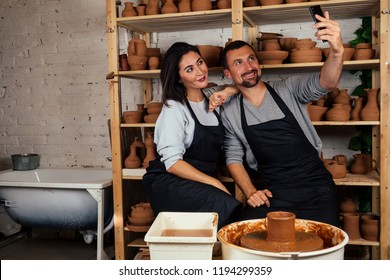 portrait of a beautiful potter woman and happy man doing selfie on the phone. artist family working with clay on a potter's wheel in the pottery workshop. love and art