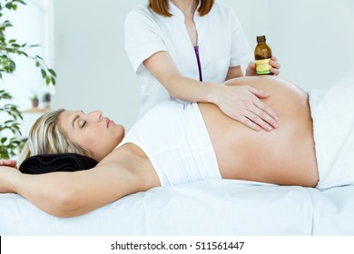 Portrait of beautiful pregnant woman having a massage in spa.