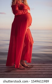 Portrait of beautiful pregnant woman in a red dress touching her stomach, standing outside by the ocean in beautiful autumn evening sunlight, stock picture.