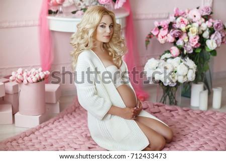 8a4c0584d46 Portrait of beautiful pregnant woman in white lingerie resting home cozy  portrait. Winter pregnancy.