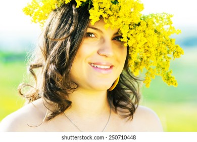 portrait of a beautiful pregnant woman with a wreath on head in the countryside