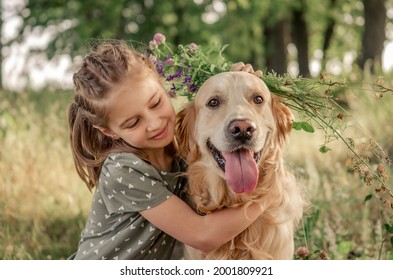 Portrait of beautiful preteen girl petting and hugging golden retriever dog looking at the camera outdoors. Kid with doggy pet in the field in summer time
