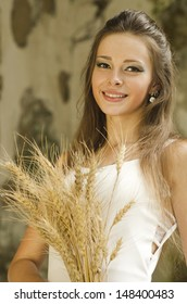 Portrait of a beautiful, pretty and smiling girl in whine modern dress with spikes of wheat