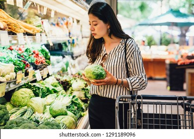 portrait beautiful pretty young woman in smart casual picking up choosing green leafy vegetables in grocery store. office lady shopping in supermarket after work. healthy care life style vegetarian.