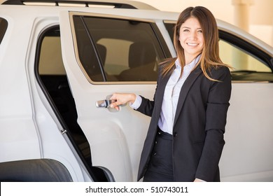 Portrait of a beautiful and professional female driver opening the car door for one of her clients