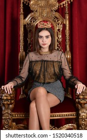 Portrait of beautiful queen sitting on throne