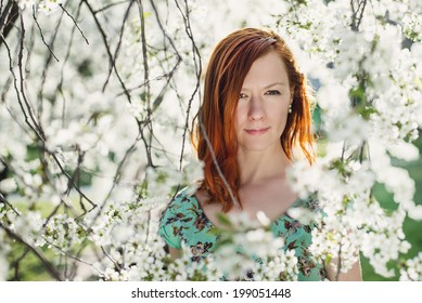 Portrait of beautiful red head girl in spring blossom