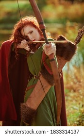 Portrait of a beautiful red-haired girl archer of the Middle Ages stands next to the lake. Celtic culture. Fantasy world.
