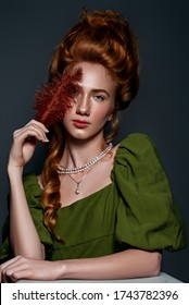 Portrait of a beautiful red-haired girl in green dress with an ultra fashionable Victorian haircut. Bohemia. Nude makeup. luxury  pearl jewelry.
