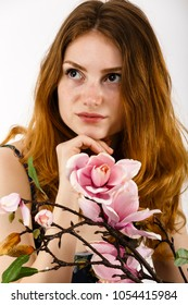 Portrait of a beautiful red-haired woman holding a flower in her hand