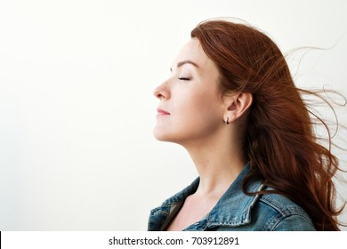 Portrait of a beautiful red-haired woman. She looks away in an inspired way, dreaming about something.